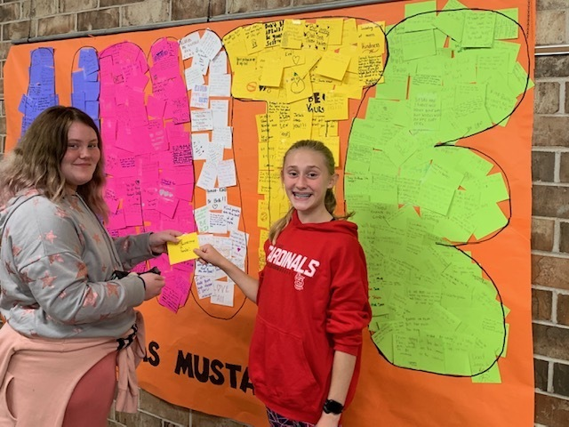 Macy Lippert and Gracie Huggins place Post-It notes on Unity mural with kindness messages to spread love and encouragement.