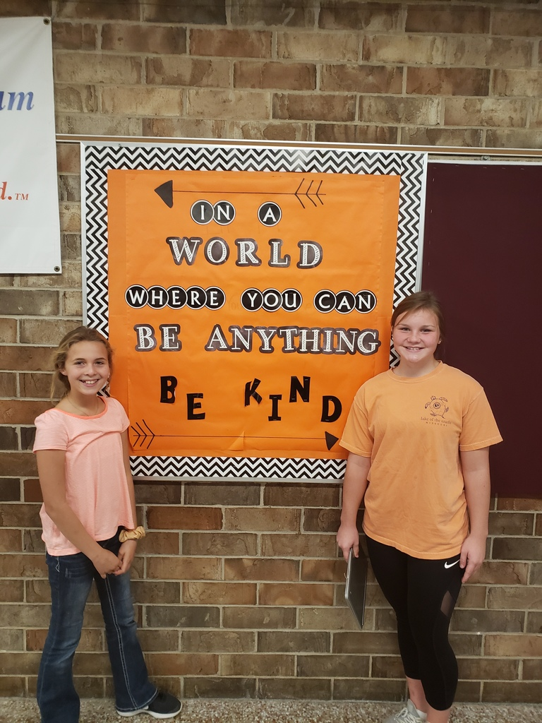Emmy Wettstein and Cora Maeder in front of Kindness bulletin board.